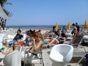 Gente escuchando en la playa las ponencias de SE-onthebeach. Imagen característica de lo que significa SE-onthebeach: congresos, playa y distensión